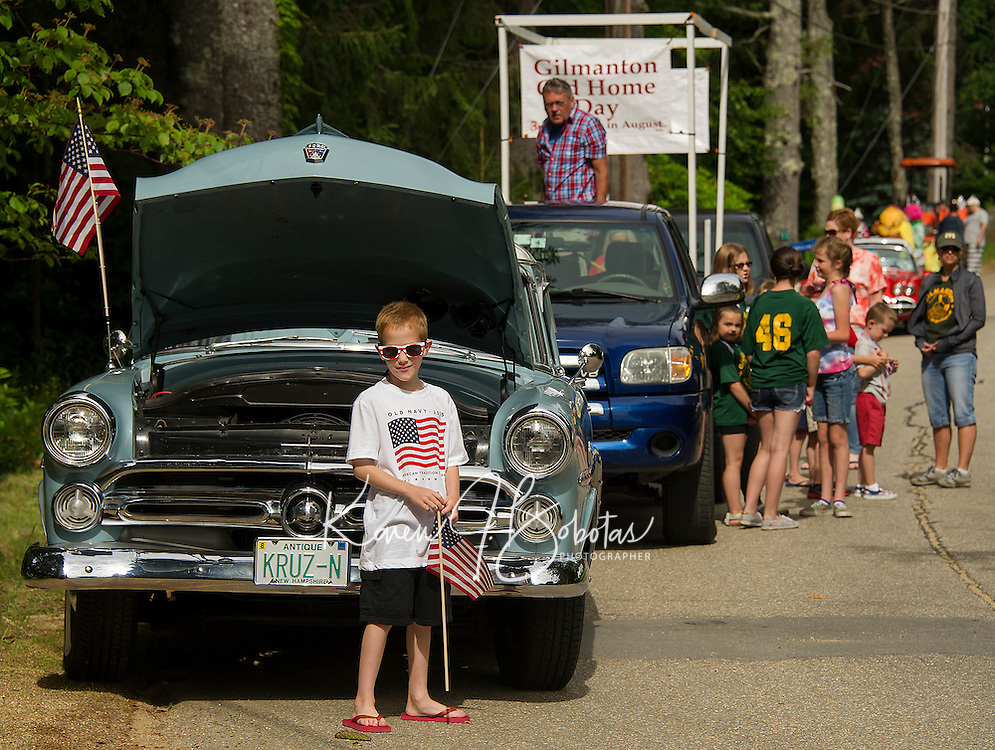 Andrew Mini stands in front of his fathers 1952 Ford as they line up along High Street for the Gilmanton 4th of July parade marching through four corners on Saturday morning.  (Karen Bobotas/for the Laconia Daily Sun)