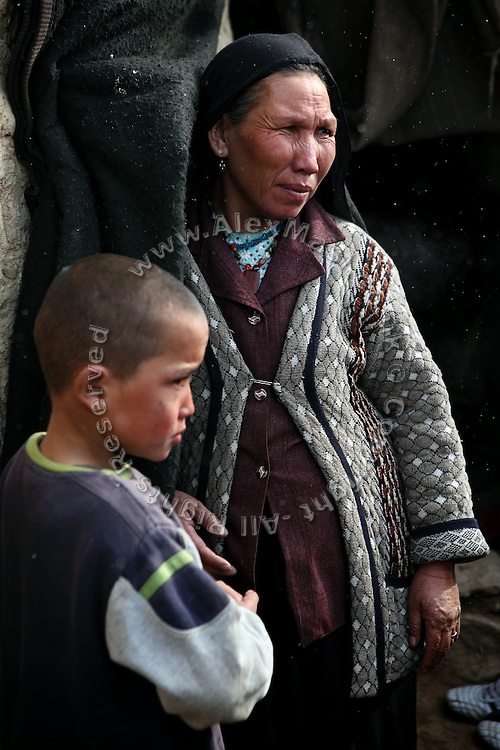 Mina, 35, (Right) is standing in front of her makeshift house built around one of the caves with her eldest son, 11,(Left) during a cold winter morning in Bamyan, central Afghanistan, an area mostly populated by Hazaras. <br /> <br /> A historically persecuted minority (15%) due to more lenient Islamic faith and characteristic 'Eastern' lineaments, Hazaras constitute the 70% of Bamyan's population.<br /> <br /> After the Taliban were driven from the region by American troops, many Internally-Displaced Persons (IDPs) returned to their homes to find them destroyed. <br /> <br /> Once a stopping point along the Silk Road between China and the Middle East, researchers think Bamyan was the site of monasteries housing as many as 5,000 monks during its peak as a Buddhist centre in the 6th and 7th centuries. <br /> <br /> It is now a UNESCO Heritage Site since 2003.
