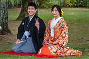 A Japanese couple kneels in formal kimonos, posing for wedding photos at Kyoto Imperial Palace (Kyoto Gosho), in Kyoto, Japan. The man gives a peace sign. Kyoto Imperial Palace (Kyoto Gosho) was the residence of Japan's Imperial Family until 1868, when the emperor and capital were moved from Kyoto to Tokyo. Kyoto Gosho is within spacious Kyoto Imperial Park (Kyoto Gyoen National Garden) which also encompasses Sento Imperial Palace. The current Imperial Palace was reconstructed in 1855 after it had burnt down and moved around town repeatedly over the centuries. The complex is enclosed by long walls and has several gates, halls and gardens. The enthronement ceremonies of Emperors Taisho and Showa were held in the palace's main hall. Tokyo Imperial Palace is now used for enthronement ceremonies. The palace grounds (but not the buildings) can now be entered and explored without joining a tour and without any prior arrangements.  To license this Copyright photo, please inquire at PhotoSeek.com.