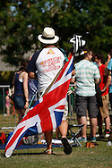Photo by Andrew Tobin/Tobinators Ltd - 07710 761829 - A competitor with Union Jack and peashooter in his back pocket during the World Peashooting Championships held at Witcham, Cambridgeshire, UK on 13th July 2013. Run in conjunction with the village fair, the Championships have been held in Witcham since 1971 when they were started by a Mr Tyson, the village schoolmaster, in order to raise funds for the village hall.Competitors come from as far afield as the USA and New Zealand to attempt to win the event. The latest technology is often used, including laser sights and titanium and carbon fibre peashooters. All peashooters must conform to strict length rules, not exceeding 12 inches, and have to hit a target 12 feet away. Shooting 5 peas at a plasticine target attached to a hay bale, the highest scorers move through the initial rounds to a knockout competition, followed by a sudden death 10-pea shootout.