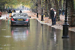 © Licensed to London News Pictures. 24/10/2019. London, UK. Police officers talk to a driver who has flooded his engine trying to pass through flood water on the roads near St James's Park in Westminster after a heavy downpour of rain. Photo credit: Ben Cawthra/LNP