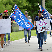 Protesters rally to end the stay at home order and open businesses and schools at Lake Eola on Saturday April 25, 2020 in Orlando, Florida.  Governor Ron DeSantis signed an executive order that restricts non-essential employees and businesses from opening and working. (Alex Menendez via AP)
