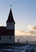 Tourist silouetted in front of Víkurkirkja church, Vík South Iceland.
