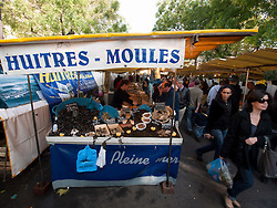Stall selling mussels and seafood at traditional market at Bastille in Paris France
