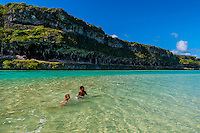 Local Kanak (Melanesian) kids playing in the water at the Lekiny Cliffs, Island of Ouvea, Loyalty Islands, New Caledonia