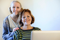 Grandmother and granddaughter with laptop, smiling, portrait