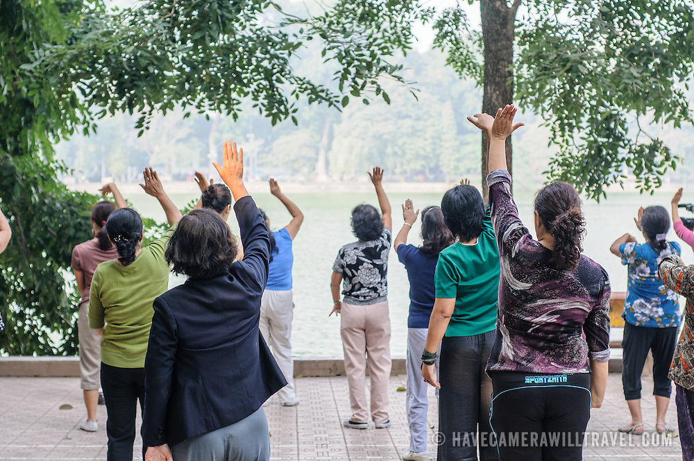 A group of local women do Tai Chi in the morning on the banks of Hoan Kiem Lake in the heart of Hanoi, Vietnam.
