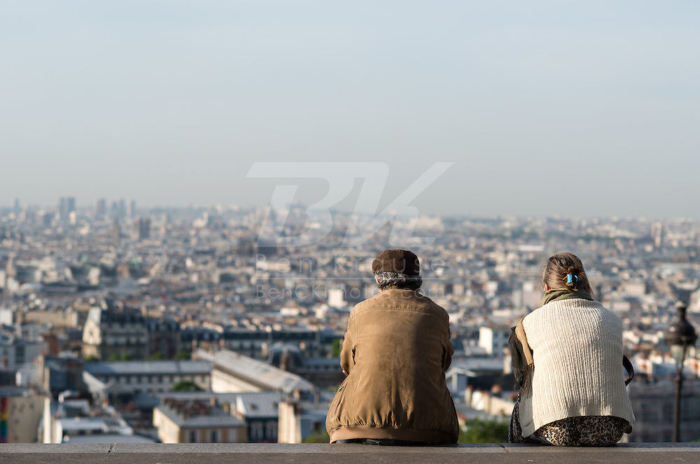 A couple sits on the steps over looking Paris, France leading up to the Sacre Coeur Basilica in Montmartre on May 19, 2012.