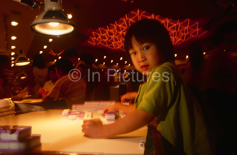 A young girl plays with Mahjong tiles at a night-club, on 10th August 1994, in Macau, China. The Macau Special Administrative Region is one of the two special administrative regions of the Peoples Republic of China PRC, along with Hong Kong. Administered by Portugal until 1999, it was the oldest European colony in China, dating back to the 16th century. The administrative power over Macau was transferred to the Peoples Republic of China PRC in 1999, 2 years after Hong Kongs own handover.