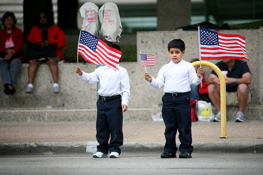6-year-old twins Jonathan, left, and Shaun Velazquez of Dallas wave flags during the Dallas Veterans Day Parade November 11, 2010.
