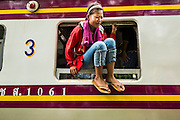 16 JUNE 2014 - ARANYAPRATHET, THAILAND:  A Cambodian girl, a migrant in Thailand, sits in the window of a train at the end of the train line in Aranyaprathet, Thailand. More than 150,000 Cambodian migrant workers and their families have left Thailand since June 12. The exodus started when rumors circulated in the Cambodian migrant community that the Thai junta was going to crack down on undocumented workers. About 40,000 Cambodians were expected to return to Cambodia today. The mass exodus has stressed resources on both sides of the Thai/Cambodian border. The Cambodian town of Poipet has been over run with returning migrants. On the Thai side, in Aranyaprathet, the bus and train station has been flooded with Cambodians taking all of their possessions back to Cambodia. PHOTO BY JACK KURTZ