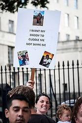 Sarah Angelina holds a banner aloft at a demonstration protesting against government rules on family migration. August 2014 UK