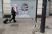 On the 10th consecutive day of protests around London by the climate change campaign Extinction Rebellion, passers-by walk past a poster about consumer waste, on 24th April 2019, at Marble Arch, London England.
