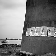A boat on the Ganga river passes by a brick kiln with IEC (Information, education and communication) material outside of Patna, Bihar.