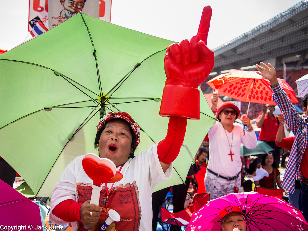 20 NOVEMBER 2013 - BANGKOK, THAILAND: A Red Shirt supporter waves a large red finger while she rallies in support of the government. Thousands of Red Shirts, supporters of the Pheu Thai ruling party in Thailand, gathered in Rajamangala Stadium in suburban Bangkok to listen to the Thai Constitutional Court deliver its verdict against the government. The court ruled that the recent efforts by the government to pass a blanket amnesty bill violated the Thai Constitution but the court did not order the party to disband or the dissolution of the government, which had been widely feared.     PHOTO BY JACK KURTZ