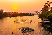 Sunset on the Thu Bon river with the sun over fish farming.