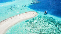 Aerial view of a sandbank, North Malé Atoll, Maldives, Indian Ocean with an anchored dhoni, boat and people swimmimg
