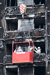 August 16, 2017 - London, England, United Kingdom - Workmen in a crane outside the Grenfell residential tower block in West London are seen wrapping the tower with a cling film type material. The tower was engulfed by a fire two months ago causing at least 80 deaths and over 70 injuries. Up to 200 survivors are still living in hotels and have resorted to searching for new homes themselves out of frustration at the council's rehousing efforts. (Credit Image: © Ray Tang/London News Pictures via ZUMA Wire)