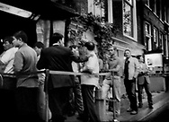 Men, mostly Chinese tourists, line up in front of a theatre advertising sex shows in Amsterdam's red light district.  The Netherlands.  The Netherlands' legal sex industry was designed to regulate prostitution, reduce sexually transmitted diseases, and human trafficking, though the presence of numerous Eastern European young men monitoring the movements of mostly female sex workers is evidence that human trafficking and organized crime involvement persists.