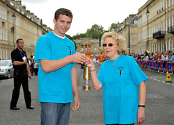 © Licensed to London News Pictures. 25/08/2012. Bath, UK. Macauley Dempsey hands over the Paralympic Flame in a lantern to Jean Meredity during a procession and celebration in Bath prior to the start of the Paralympic Games 2012.  25 August 2012..Photo credit : Simon Chapman/LNP