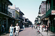 Tourists walking down street past bars Bourbon Street, French Quarter, New Orleans, Louisiana, USA 1976