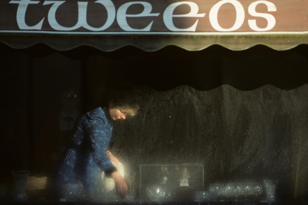 Ireland, County Galway, Clifden, Shopkeeper dusts crystal in store window on autumn morning