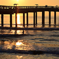 The St. Johns County Ocean Pier silhoutted against sunrise with people, St. Augustine Beach, Florida