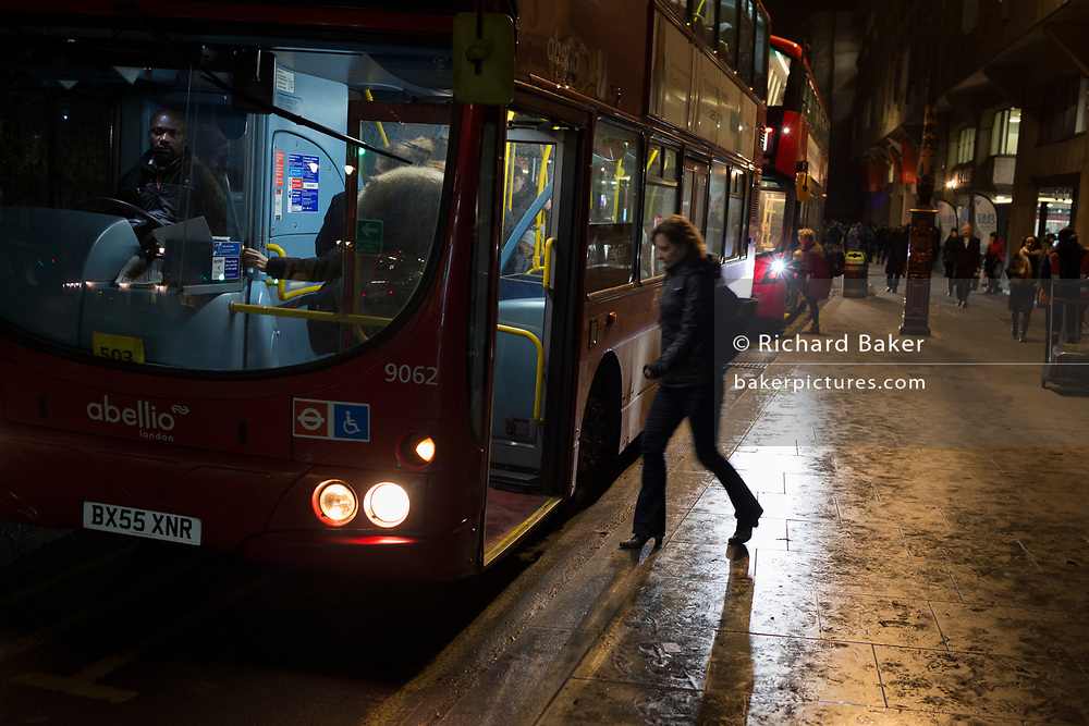 Commuters board a London bus in winter darkness on the Strand, on 12th December 2017, in London England.