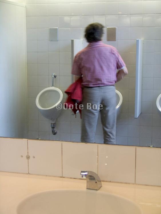 man just finishing urinating