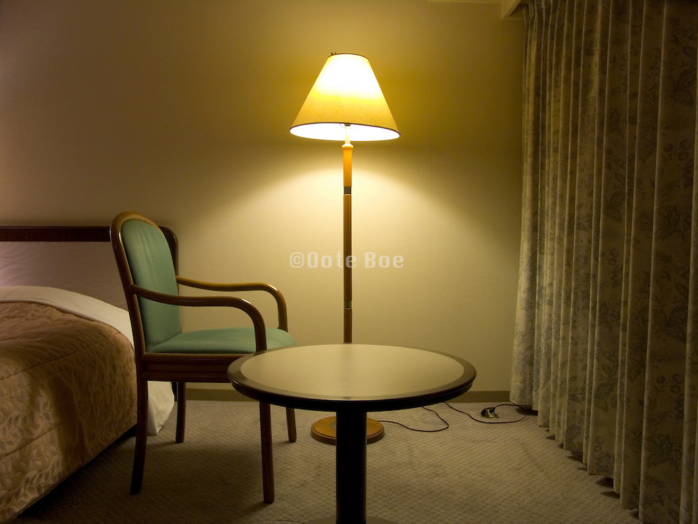 hotel room during the night with one chair facing the window curtains