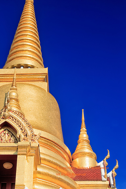 Stupa in Profile: Looking up, two brilliantly gold Stupas are set against a vibrantly blue sky, at Tritotsathep Temple, Bangkok Thailand.