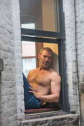 hot shirtless older man sitting on a window ledge in New York City