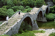 """Visit Kalogeriko triple-arch stone bridge, 300 years old, near Kipi, in Zagoria, Epirus/Epiros, Greece, Europe. Zagori (Greek: ) is a region and a municipality in the Pindus mountains in northwestern Greece. Zagori contains 45 villages collectively known as Zagoria (Zagorochoria or Zagorohoria). Published in """"Pindos: The National Park"""" (2010) by Alexander G. Tziolas, preface by Tom Dempsey et al, ISBN 978-960-98795-3-8."""