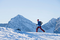 Skier climbing up on snow covered mountain