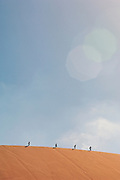 Tourists walking along the crest of a huge sand dune in the Namib Desert near Swakopmund, and area famous for sandboarding, Namibia