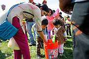 Children surround a water bucket to fill their water guns as more than 1,500 participants throw colored powder on each other to celebrate the end of Winter and beginning of Spring during Holi, a Hindu Festival of Colors, at Cardoza Park in Milpitas, California, on March 23, 2013. (Stan Olszewski/SOSKIphoto)