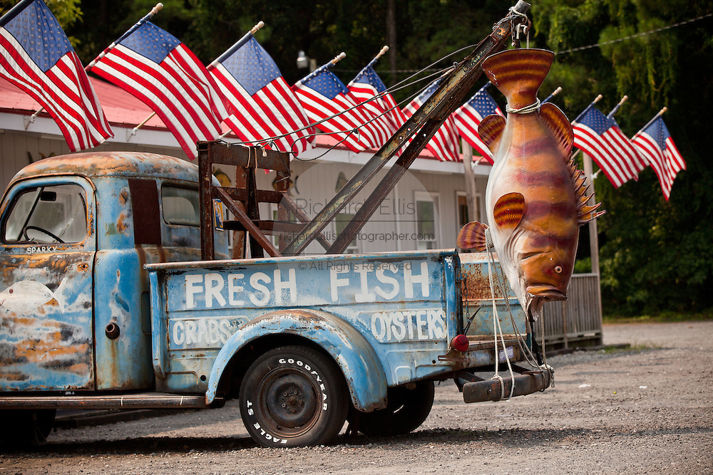 A tow truck holding a giant fiberglass fish for a local fish restaurant in Pawley's Island, SC.