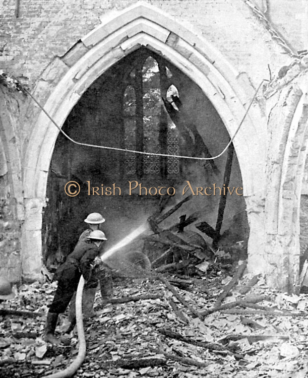 British fire-fighters damping down smouldering roof timbers of  a church hit by German bombs: June 1940. World War II.