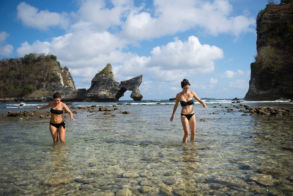 Nusa Penida, Indonesia - October 1, 2017: Margaux and Helene, friends from France, walk carefully in the rocky shallows at Atuh Beach on the island of Nusa Penida near Bali.