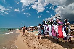 Salento - Puglia - Marina di Pescoluse - Venditore mostra la merce a potenziali clienti.