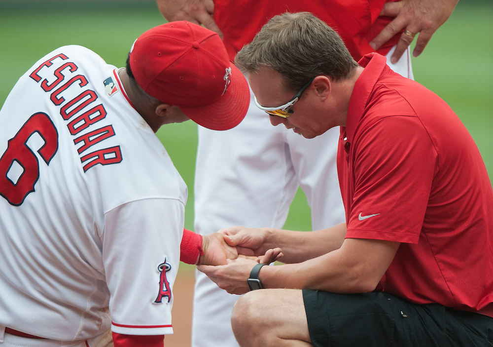 Angels' trainer Adam Nevala examines Yunel Escobar after he was injured in the third inning against the Houston Astros Sunday at Angel Stadium. <br /> <br />  //ADDITIONAL INFO:   <br /> <br /> angels.0530.kjs  ---  Photo by KEVIN SULLIVAN / Orange County Register  -- 5/29/16<br /> <br /> The Los Angeles Angels take on the Houston Astros Sunday at Angel Stadium.