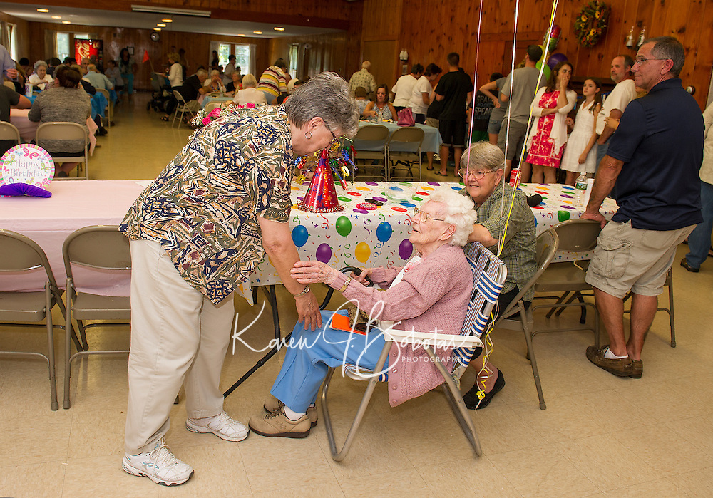 Marena Schultz wishing Gladys Burbank a happy birthday with her daughter Brenda Moulton by her side during her surprise 100th birthday celebration at Leavitt Park on Saturday afternoon.  (Karen Bobotas/for the Laconia Daily Sun)