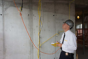 Investigative Engineering Services, Assistant Commissioner Tim Lynch inspects wiring on a new construction site in Manhattan, New York City. Inspecting new yellow-coded wiring, Tim works in the prevention of damage to old and ensuring new buildings are up to standard plus often, assessing the status of a collapsed structure. From the chapter entitled 'The Skyline' and from the book 'Risk Wise: Nine Everyday Adventures' by Polly Morland (Allianz, The School of Life, Profile Books, 2015). <br /> ,