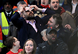 An Arsenal fan holds bank notes against his head in frustration during the Carabao Cup Semi Final, First Leg match at Stamford Bridge, London.