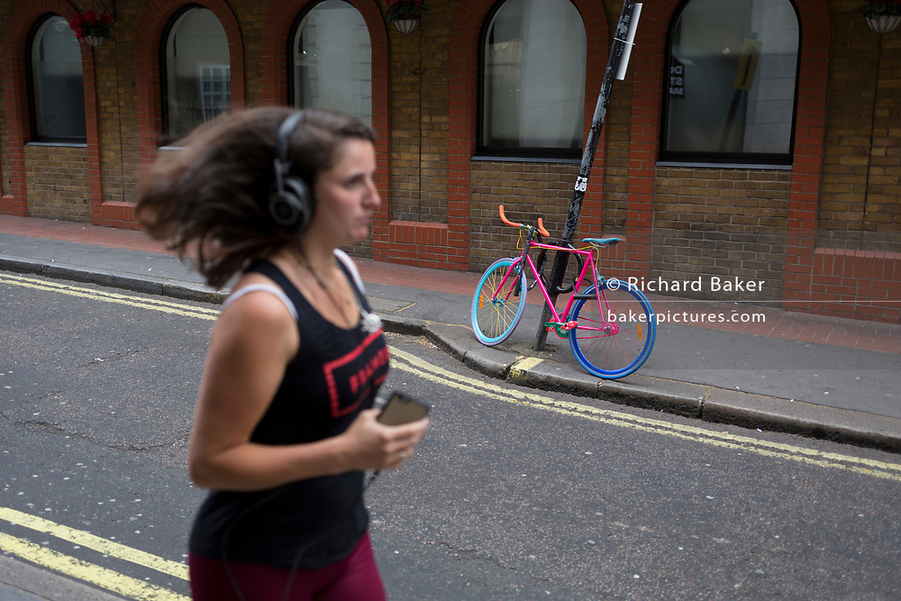 A runner passes a multi-coloured bike locked to a post in a sidestreet in London's West End, on 29th April 2019, in London, England.