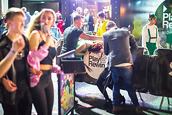© Licensed to London News Pictures . 27/12/2017. Wigan, UK. A woman is tended to as she bends over a railing. Revellers in Wigan enjoy Boxing Day drinks and clubbing in Wigan Wallgate . In recent years a tradition has been established in which people go out wearing fancy-dress costumes on Boxing Day night . Photo credit: Joel Goodman/LNP