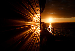 © Licensed to London News Pictures.06/08/15<br /> Saltburn, UK. <br /> <br /> Evening sun reflects off the shutters of the amusements on the pier at sunset at Saltburn by the Sea in Cleveland. <br /> <br /> Photo credit : Ian Forsyth/LNP