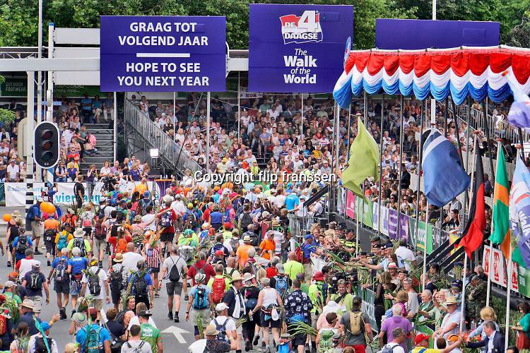 Nederland, Nijmegen, 19-7-2018Intocht van de wandelaars in Nijmegen op de vierde dag van de 103e 4Daagse . Het vierdaagselegioen loopt over de Via Gladiola Nijmegen binnen. Na een feestelijke intocht volgt de uiteindelijke finish en het ophalen van het kruisje, vierdaagsekruisje, op de Wedren. Iedere deelnemer krijgt een bloem, gladiool, uitgerijkt. Ook rolstoelers komen binnen. Rolstoel deelnemer.Foto: Flip Franssen