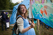A pregnant woman with a banner next to the Cuadrilla site. Anti-fracking activists join hands to surround the Cuadrilla fracking site. Thousands turned out for a march of solidarity against fracking in Balcombe. The village Balcombe in Sussex is the  centre of fracking by the company Cuadrilla. The march saw anti-fracking movements from the Lancashire and the North, Wales and other communities around the UK under threat of gas and oil exploration by fracking.