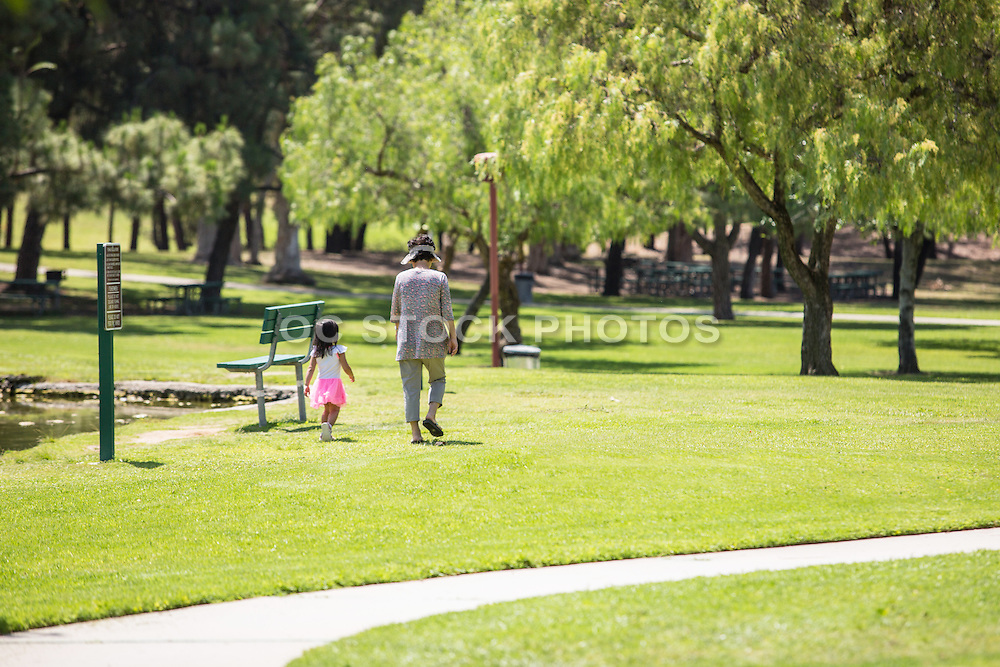 Mom and Young Daughter Enjoying a Walk at  Ralph B. Clark Regional Park in Buena Park